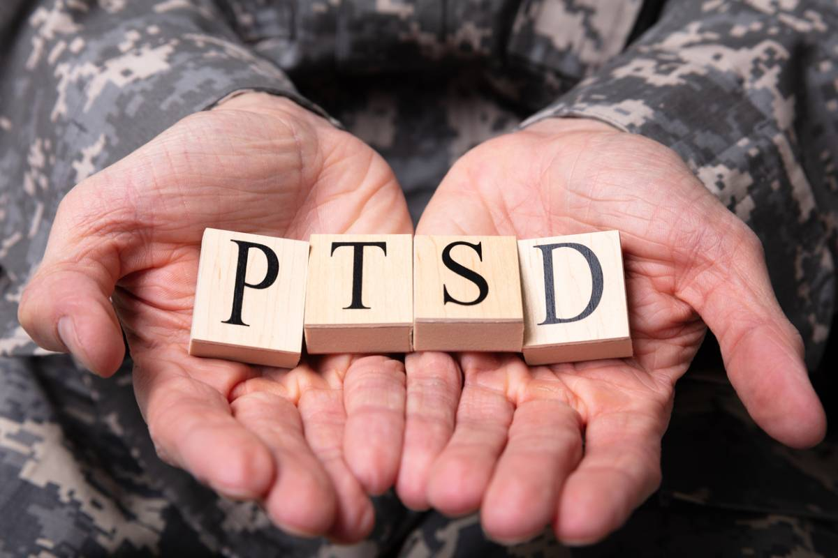 Hands showing PTSD written out in tiles.